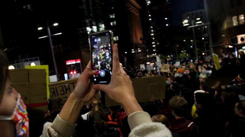a man holding a phone in front of a crowd: A protester takes a photo with her phone in Martin Place during a 'Black Lives Matter' rally on June 02, 2020 in Sydney, Australia. The event was organized to rally against aboriginal deaths in custody in Australia as well as in solidarity with protests across the United States following the killing of an unarmed black man George Floyd at the hands of a police officer in Minneapolis, Minnesota.