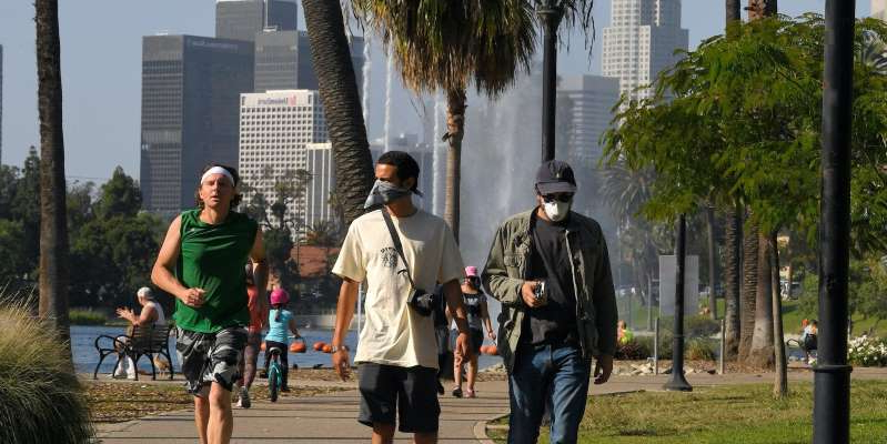 a couple of people that are standing in the grass: As the coronavirus pandemic continues, California has taken steps to reopen certain industries. Mark J. Terril/AP Photo