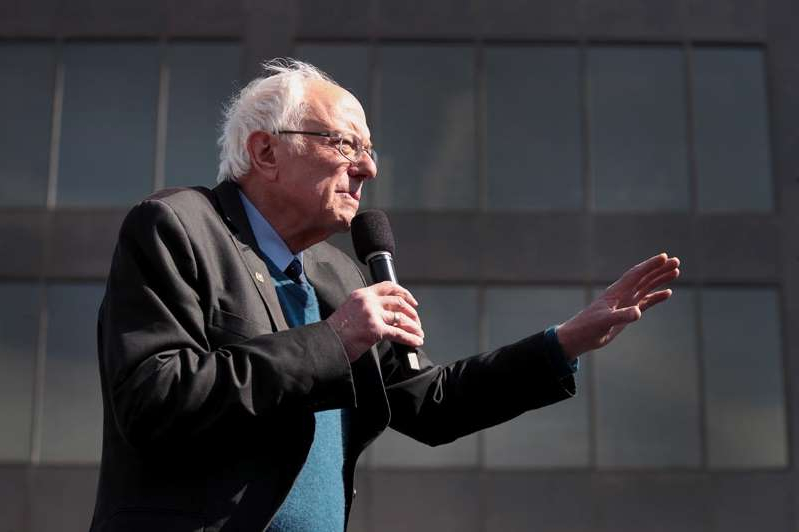 a man talking on a cell phone: Then-Democratic presidential candidate Bernie Sanders speaks to supporters in Michigan during a March rally.