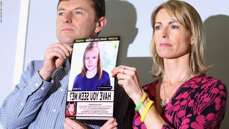 a person holding a sign: Kate and Gerry McCann hold an age-progressed police image of Madeleine during a news conference in London to mark the 5th anniversary of her disappearance in May 2012.