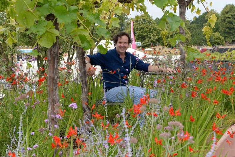 Diarmuid Gavin holding a flower garden: Garden designer and Daily Mirror columnist Diarmuid Gavin at the Hampton Court Flower Show.