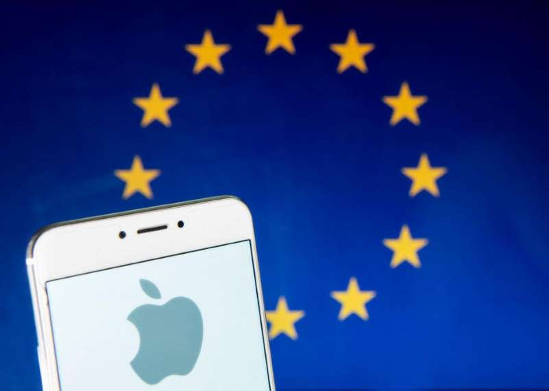 a sign in front of a laptop: Apple is under the microscope in Europe. Budrul Chukrut/SOPA Images/LightRocket via Getty Images