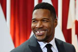 Michael Strahan wearing a suit and tie smiling at the camera