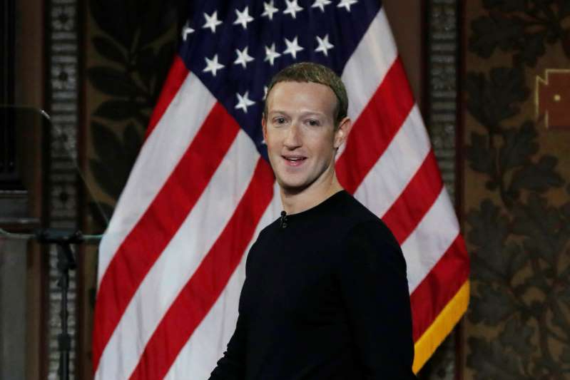 Mark Zuckerberg standing in front of a flag
