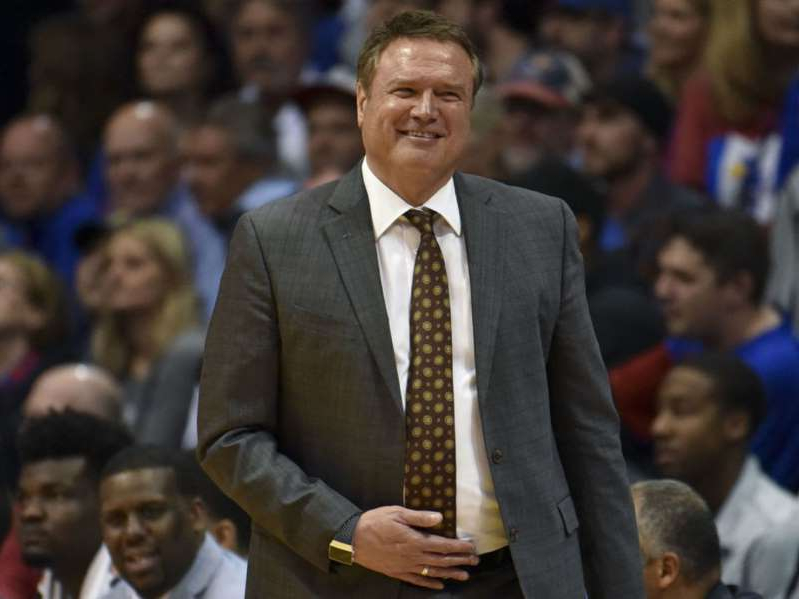 Bill Self in a suit standing in front of a crowd