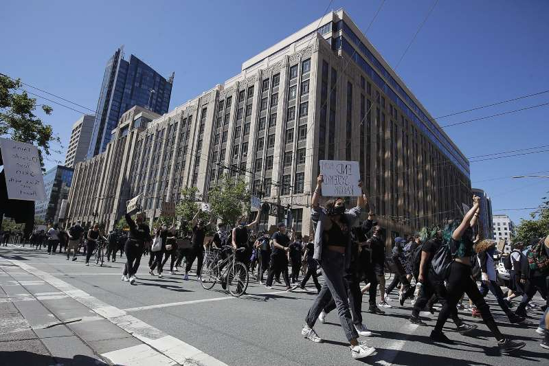 a group of people walking in front of a building: People march on Market Street in San Francisco, Saturday, June 13, 2020, at a protest over the Memorial Day death of George Floyd, who died after being restrained by Minneapolis police.