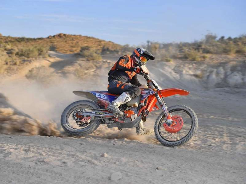 a man riding a motorcycle down a dirt road: Riding DT Racing's 2020 KTM 450 SX-F Factory Edition in the high desert of Southern California.