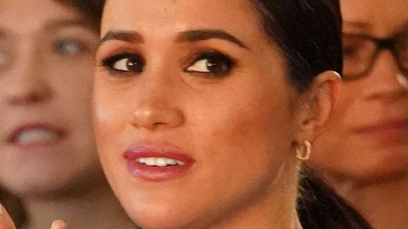 a close up of Meghan Markle who is smiling and looking at the camera