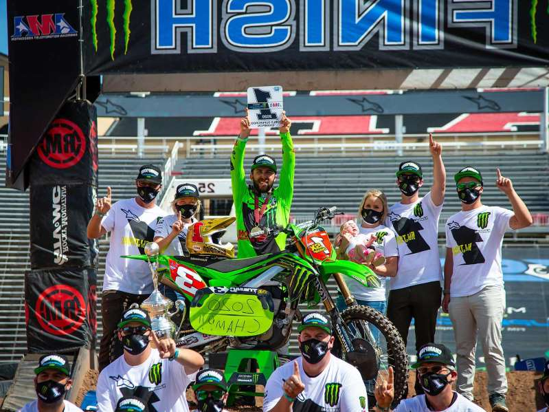 a group of people standing in front of a crowd: Monster Energy Kawasaki's Eli Tomac piloted his KX450 to a fifth place finish at Salt Lake City 7, which was more than enough to clinch his first premier class Monster Energy AMA Supercross title.