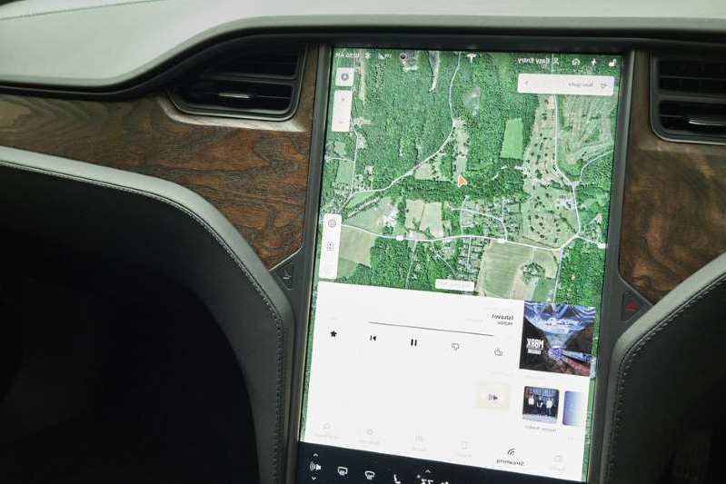 an open laptop computer sitting on top of a car: The big touchscreen handles a lot of functions in the Model S. Tim Stevens/Roadshow