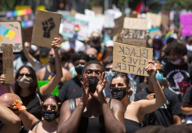 a group of people standing in front of a crowd: People take part in an All Black Lives Matter march, organized by Black LGBTQ+ leaders, in the aftermath of the death in Minneapolis police custody of George Floyd, in Hollywood, Los Angeles, California, U.S., June 14, 2020. REUTERS/Ringo Chiu