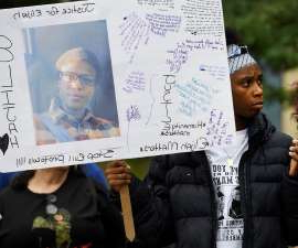 a man holding a sign posing for the camera: Everything you need to know about Elijah McClain's murder, including ways you can get involved.