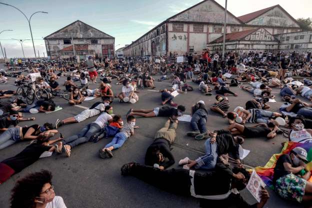 a group of people sitting in a parking lot in front of a crowd: Demonstrators in Recife, Brazil, demand justice for the death of 5-year-old Miguel Otávio Santana da Silva, the son of a black maid who fell from the ninth floor of a building while under the watch of his mother's white employer.