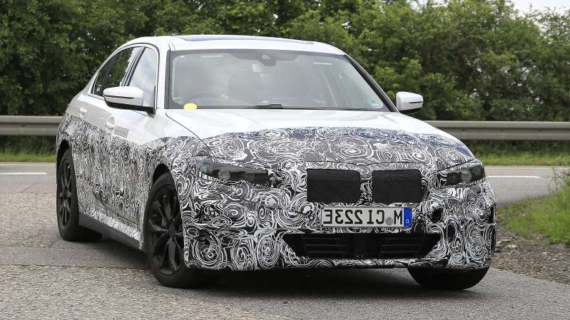 a car parked on the side of a road: Electric BMW 3 Series in development - front
