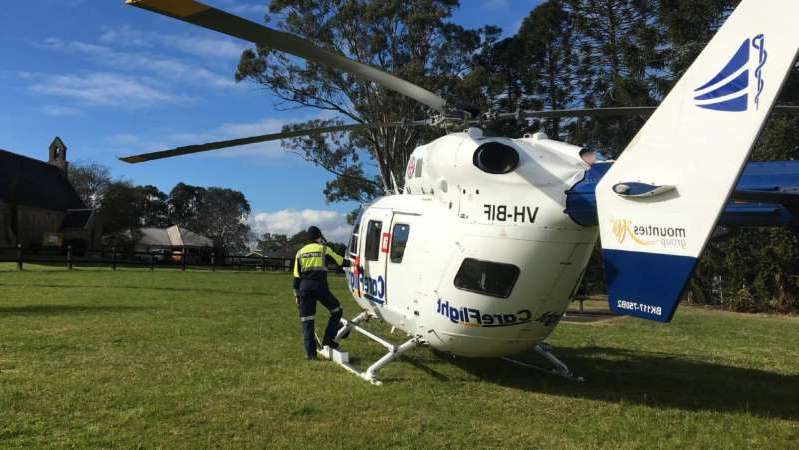a small plane sitting on top of a grass covered field: CareFlight's Rapid Response Helicopter landed in a clearing near the incident. (Supplied: CareFlight)