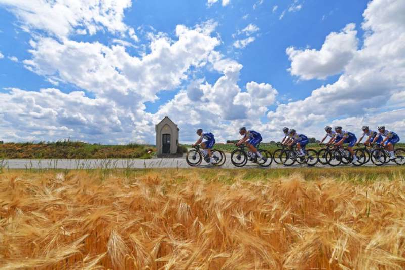 a close up of a dry grass field: Members of the Deceuninck-QuickStep team train in Belgium ahead of the restart of the 2020 racing season