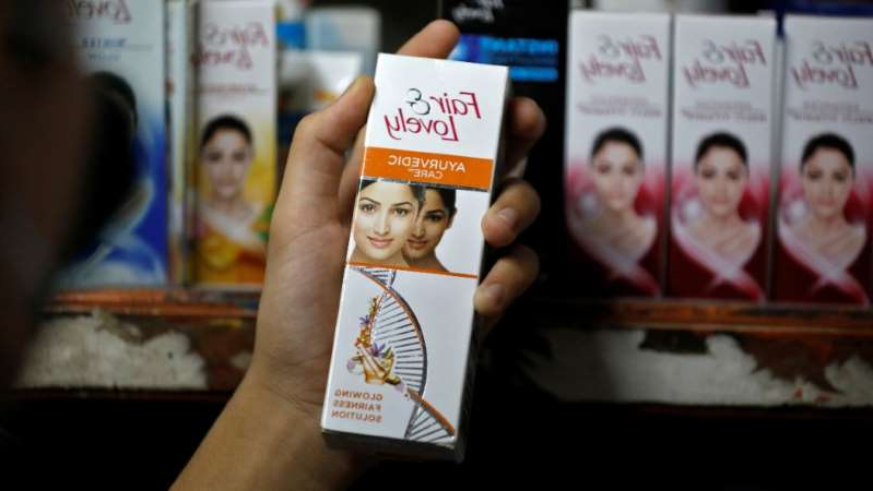A customer picks up Fair & Lovely brand of skin lightening product from a shelf in a shop in Ahmedabad, India, on June 25, 2020.