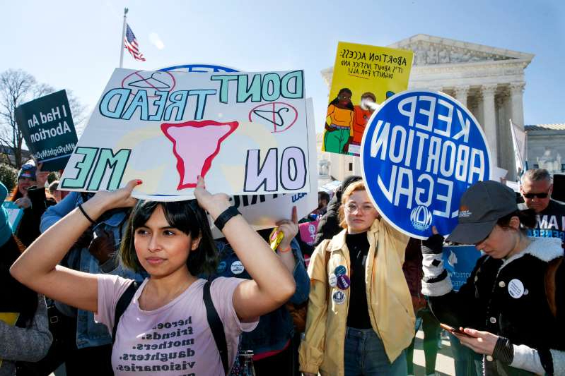 a group of people holding a sign posing for the camera: Abortion rights demonstrators including Jaylene Solache, of Dallas, Texas, right, rally outside the Supreme Court in Washington, D.C., on March 4, 2020.