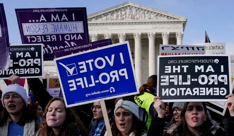 a group of people standing in front of a sign posing for the camera: Anti-abortion marchers rally at the Supreme Court during the 46th annual March for Life in Washington, U.S., January 18, 2019.