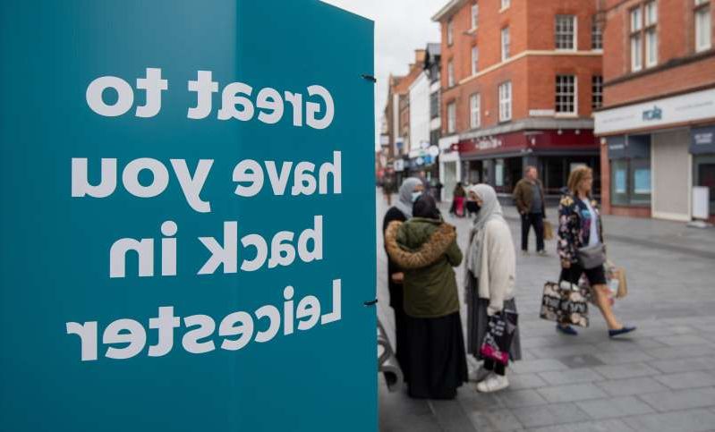 a group of people standing in front of a sign: Signs in the centre of Leicester welcoming people back as the city may be the first UK location to be subjected to a local lockdown after a spike in coronavirus cases (Joe Giddens/PA)