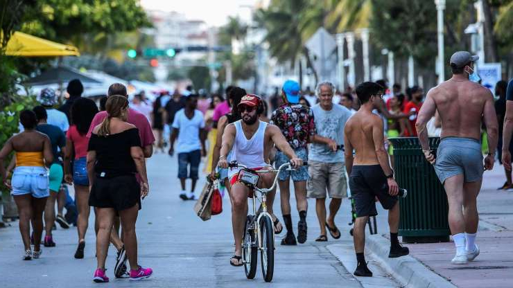 a group of people walking down the street: A man rides a bicycle as people walk on Ocean Drive in Miami Beach, Fla. on June 26, 2020.