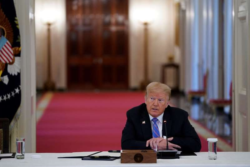 Donald Trump wearing a suit and tie sitting at a table: President Trump listens during a meeting with the American Workforce Policy Advisory Board in the East Room of the White House in Washington on June 26.