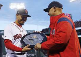 a man holding a baseball bat: FILE - In this April 11, 2019, file photo, Boston Red Sox manager Alex Cora, left, presents right fielder Mookie Betts with the 2018 AL MVP Award before a baseball game between the Red Sox and the Toronto Blue Jays at Fenway Park in Boston. The award includes the name and image of Kenesaw Mountain Landis. (AP Photo/Winslow Townson, File)