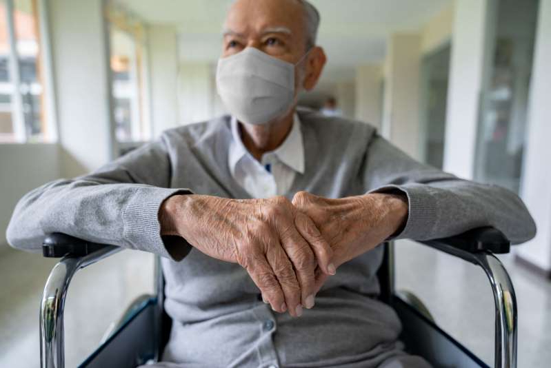 a man sitting in a room: Senior adult in a wheelchair at the hospital wearing a facemask to avoid coronavirus – pandemic lifestyle concepts
