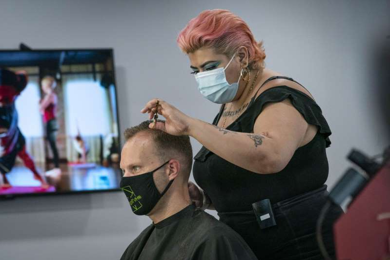 a man standing in front of a mirror posing for the camera: A hairstylist wearing a protective mask gives a customer a haircut at a salon in Washington, D.C., U.S., on Monday, June 22, 2020. Mayor Muriel Bowser on Friday announced the loosening of restrictions that allows certain businesses to reopen with restrictions and activities to resume with safety precautions as part of the phase two of reopening in the wake of the coronavirus pandemic.