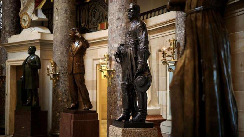 a person standing next to a fireplace: A statue of Joseph Wheeler (3rd R), a cavalry general in the Confederate States Army during the Civil War and member of the House of Representatives, is on display in Statuary Hall inside the U.S. Capitol earlier this month in Washington, DC.