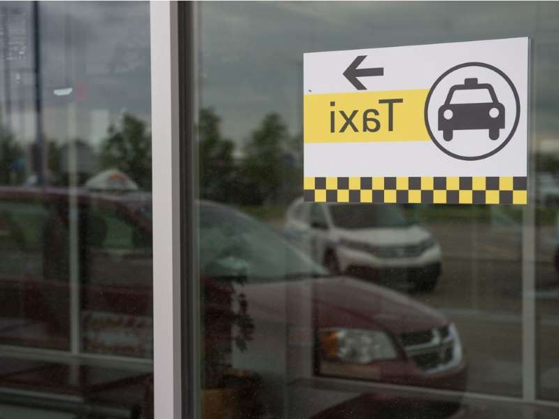 a sign in front of a window: A taxi sign can be seen on the window of the Regina International Airport in Regina, Saskatchewan on June 30, 2020. In the reflection of the window, a Captial Cabs taxi can be seen.
