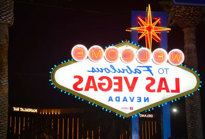 a sign lit up at night with Welcome to Fabulous Las Vegas sign in the background: For the first since time the NHL began its return-to-play plan, Vegas might no longer be a lock to be one of the league's hub cities.