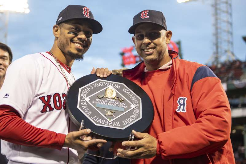 Alex Cora, Mookie Betts are posing for a picture: Mookie Betts, right, receives his 2018 MVP plaque, which is inscribed as the Kenesaw Mountain Landis Memorial Baseball Award. (Photo by Billie Weiss/Boston Red Sox/Getty Images)