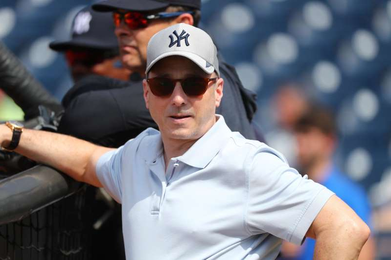 Brian Cashman holding a baseball bat: Brian Cashman provided an update on MLB teams' procedure should a player contract COVID-19.