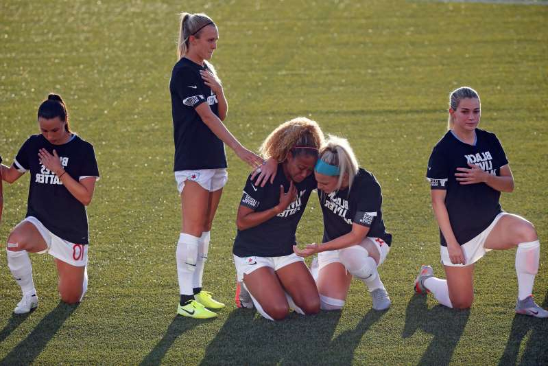 Kealia Ohai et al. playing football on a field: Casey Short, Julie Ertz and most of their teammates knelt during the anthem. One did not. (AP Photo/Rick Bowmer)