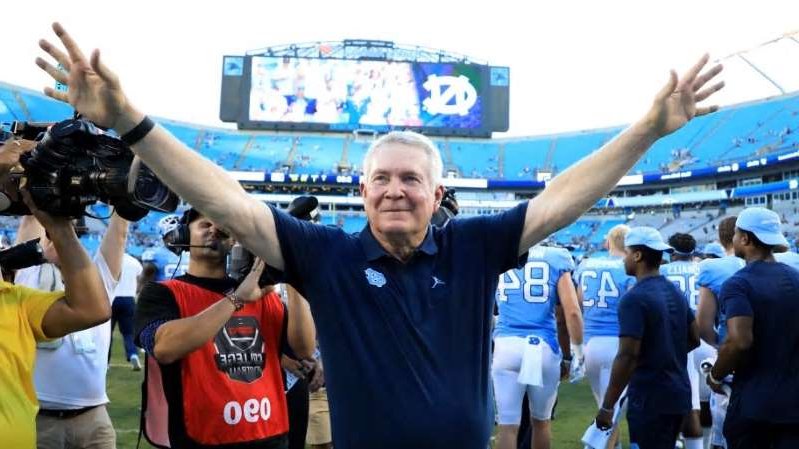 Mack Brown standing in front of a crowd