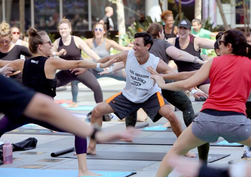 a group of people playing a sport: LOS ANGELES, CA - SEPTEMBER 07: Guests attend a Free Community Workout lead by Fitbit Local Ambassadors Blake Raymond, Elise Joan, Mike Sherbakov and Sheri Matthews-Kimmel on Sept. 7, 2019 at L.A. LIVE to support the launch of Fitbit's newest product the Versa 2 on September 7, 2019 in Los Angeles, California. (Photo by Rachel Murray/Getty Images for Fitbit Local)