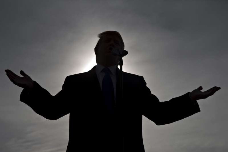 a man standing in front of a cloudy sky: The silhouette of Donald Trump, president and chief executive of Trump Organization Inc. and 2016 Republican presidential candidate, is seen as he speaks during a campaign rally at Dubuque Regional Airport in Dubuque, Iowa, U.S., on Saturday, Jan. 30, 2016. A