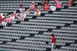 a group of people walking on the roof of a building: Los Angeles Angels designated hitter Shohei Ohtani (17) looks for stray baseballs in the stands near cutouts of fans during practice at Angels Stadium on Friday, July 3, 2020, in Anaheim, Calif. (AP Photo/Ashley Landis)