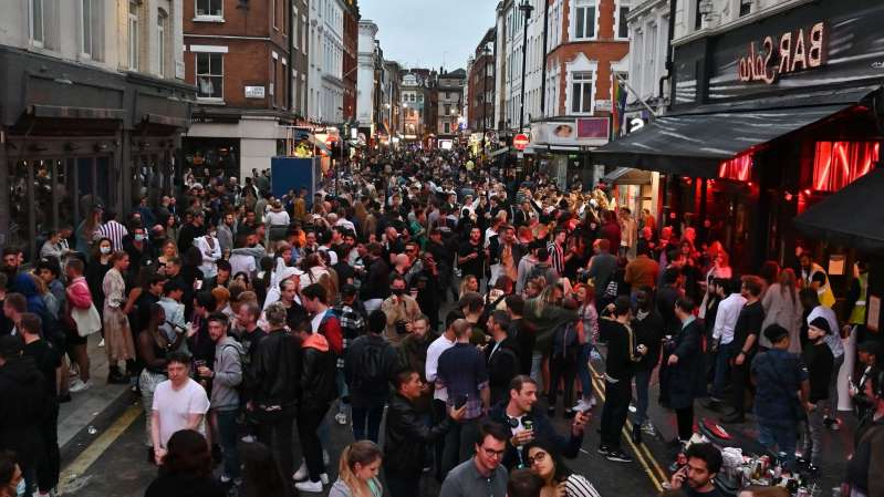 a large crowd of people walking down a street: People were seen enjoying their new freedoms in Soho as lockdown restrictions were lifted in England