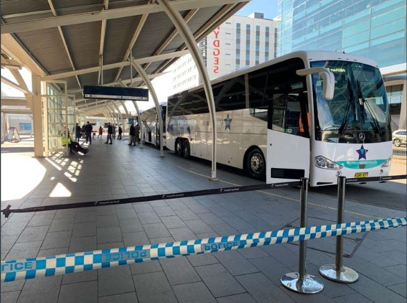 a passenger bus that is parked on the side of a building: Sydney International Airport was even quieter than usual this morning. The airport is currently operating at just one per cent of pre-pandemic levels.