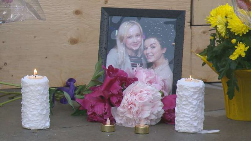 a person sitting at a table with a birthday cake: A memorial photo of Georgia Donovan and Emma Macarthur at the site of the crash that took their lives in south central Edmonton.