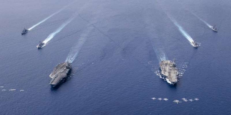 a plane flying over a body of water: Aircraft in formation over the USS Nimitz and USS Ronald Reagan. U.S. Navy photo by Mass Communication Specialist 3rd Class Keenan Daniels