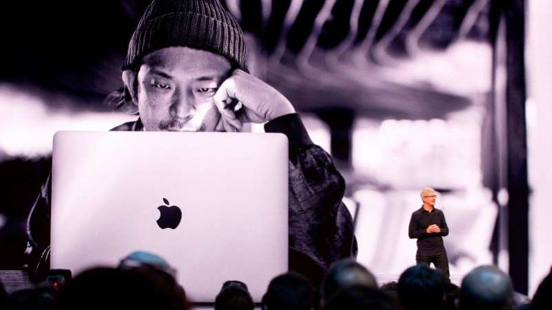 a man standing in front of a laptop: Apple CEO Tim Cook on-stage at last year's Worldwide Developers Conference.