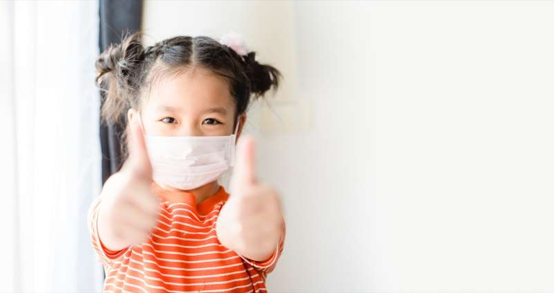 a woman wearing a white shirt: Child wearing a mask giving a thumbs up