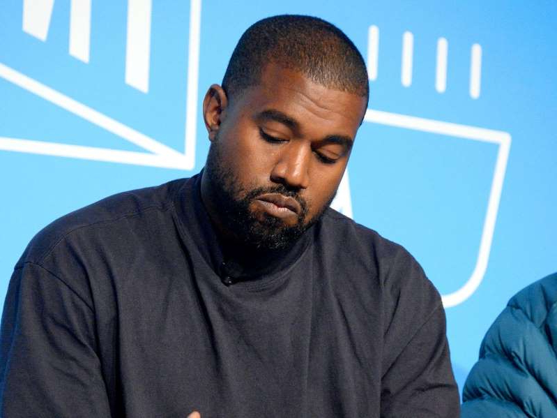 Kanye West in a blue shirt: Kanye West speaks on stage at the