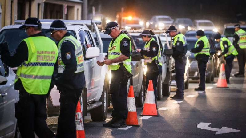 a group of people wearing costumes: Police stop and question drivers at a checkpoint in Albury yesterday on the first day of on new border restrictions between NSW and Victoria.