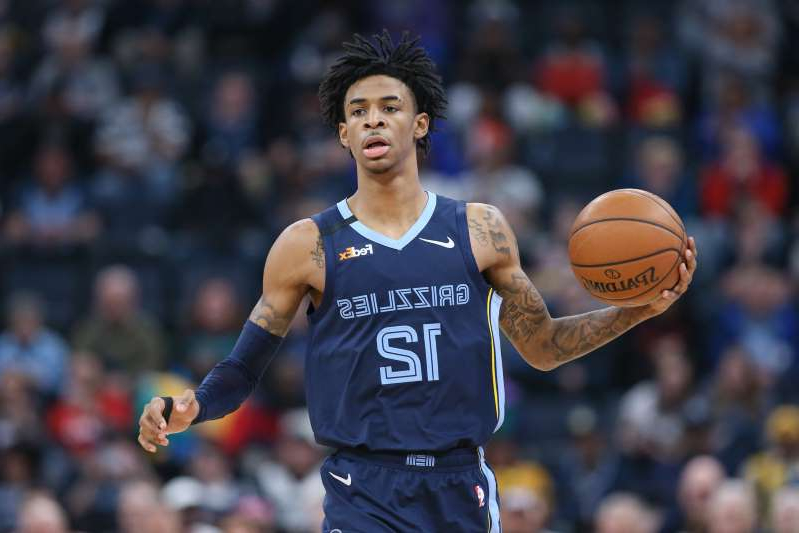 a man holding a basketball: Before heading to Orlando for the NBA restart, Ja Morant surprised his dad with a new car.