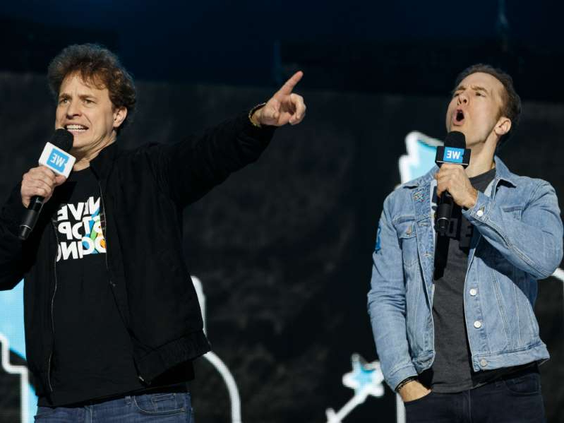 Marc Kielburger standing on a stage: We just need WE co-founders Craig and Marc Kielburger to come out on a stage and say,