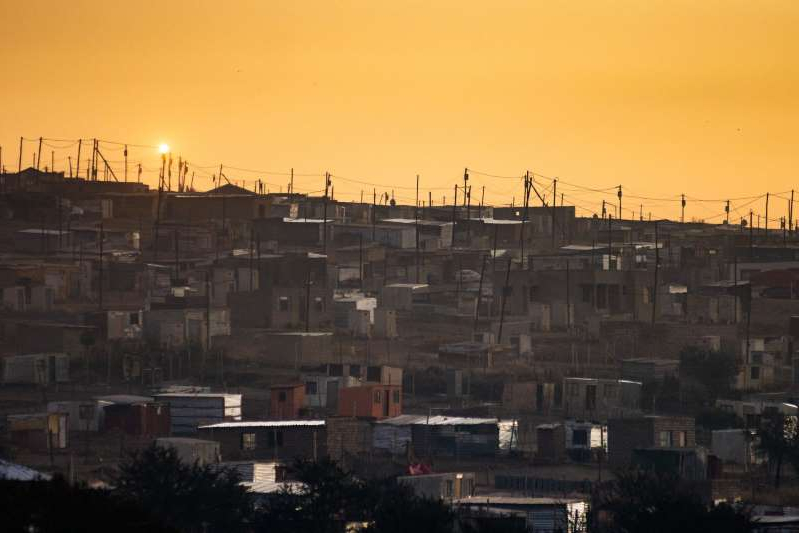 a large tower in a city: Electricity cables run above residential shacks as the sun rises in the Saulsville township, Pretoria, South Africa, on Friday, May 31, 2019. While South African President Cyril Ramaphosa says power utility Eskom Holdings SOC Ltd. is considered too big to fail, it could be too big to support because of the costs associated with stabilizing its finances, Engineering News reported, citing S&P Global Ratings Director Ravi Bhatia.